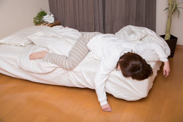 ベッドから落ちそうな位置でうつ伏せになっている女性の写真