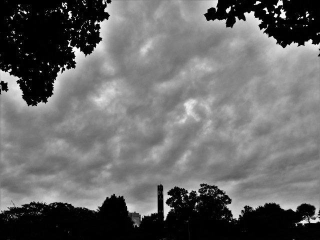 どんよりとした雲が街の空にたちこめるモノクロの風景写真