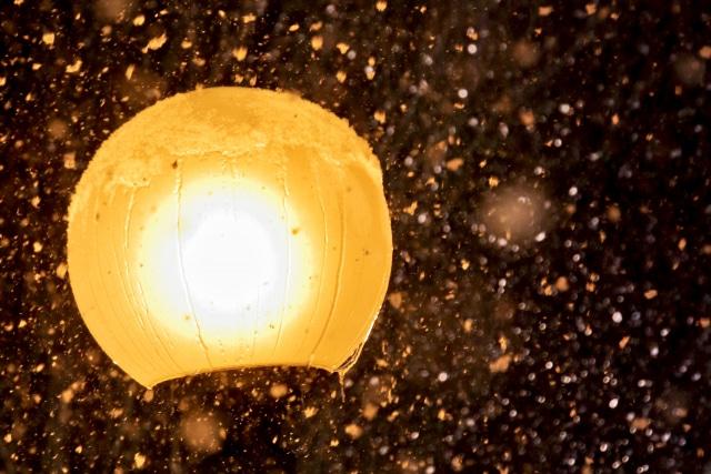 街灯の周りを雪が舞う写真