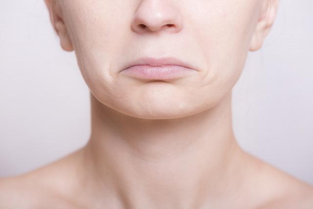 口をへの字に結んだ女性のアップ写真