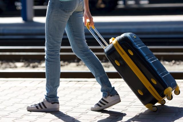 スーツケースを引いて歩く人の下半身の写真