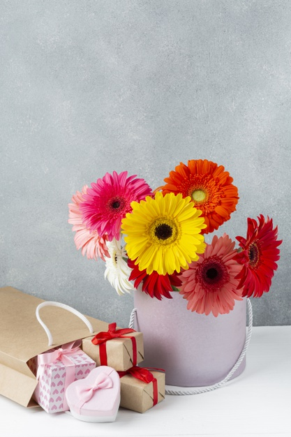 gerbera-daisy-flowers-bucket-with-small-gift-boxes-nearby_23-2148268321.jpg