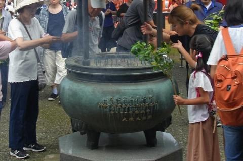 香炉の煙を浴びる人