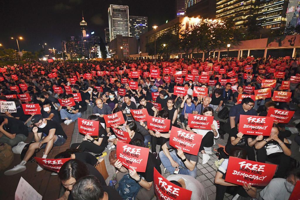 0001p1_「逃亡犯条例」改正案の完全撤回などを求めた民主派団体の集会で、「香港を解放せよ 今すぐ民主主義を」と書かれたプラカードを掲げる人たち=26日、香港(共同)