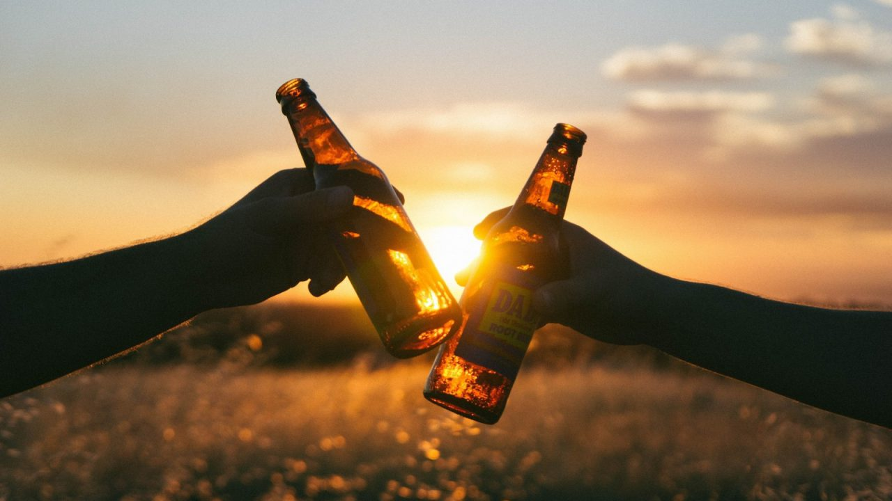 friends-toasting-with-beer-bottles-in-meadow-at-sunset-1280x720.jpg